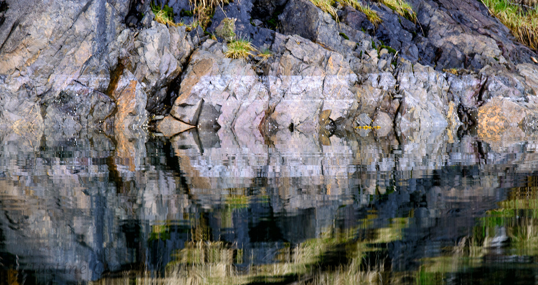 Rocky shore and reflections in Prince William Sound, Alaska
